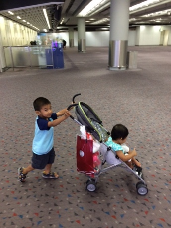 Pushing his sister around HK Airport